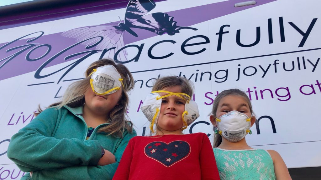 Three girls under 12 are wearing dust masks over there faces to supposedly protect them from the corona virus.  However, just like the Three Wise Monkeys, one girl covers her eyes, another her ears, and the last her mouth.