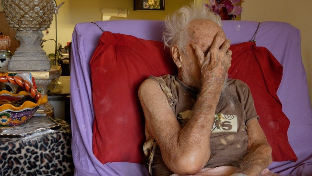 Elderly man covers his face in frustration with his care at assisted living center